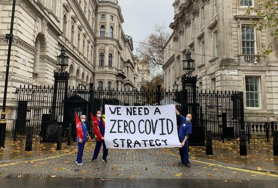 Health workers outside Downing Street holding a 'We need a Zero Covid Strategy' banner