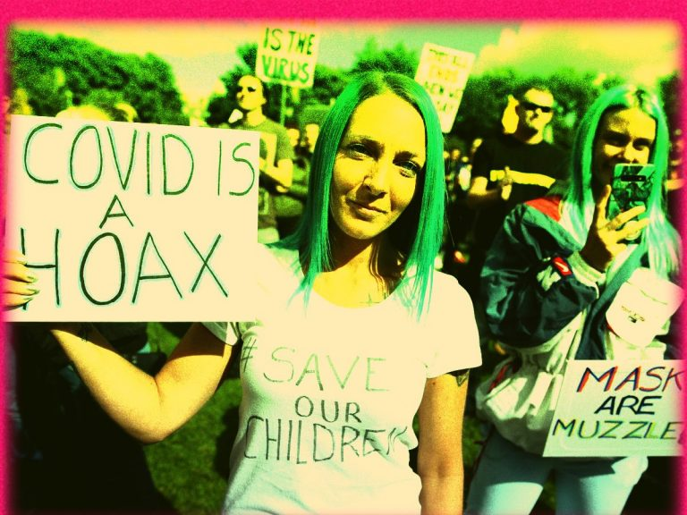 An image of a Covid denier holding a sign which says 'Covid is a hoax'