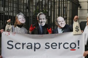 An image of people wearing facemasks of Dido Harding, Matt Hancock and Rupert Soames holding a banner which says 'Scrap Serco'.