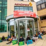 """Protesters sitting outside the AstraZeneca office with a banner which says """"End vaccine apartheid. We demand a people's vaccine!"""""""