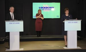 Nicola Sturgeon giving a press conference. On the rostrum is the slogan 'Stay home'.