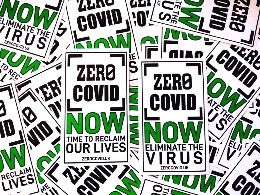 """An image of a lot of Zero Covid stickers with the slogans """"Zero Covid Now, time to reclaim our lives"""" and """"Zero Covid Now, eliminate the virus"""""""